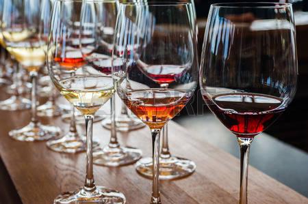 52146890-tre-bicchieri-di-vino-con-il-bianco-rosa-e-campioni-di-vino-rosso-sul-bancone-di-legno-con-altri-vet